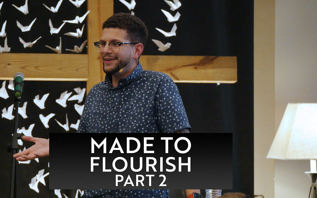 """Pastor Jacob preaching his message from Made to Flourish. Wooden cross with black backdrop and white, folded origami cranes are in the background. The words """"Made to Flourish, Part 2"""" are on the bottom third of the image."""