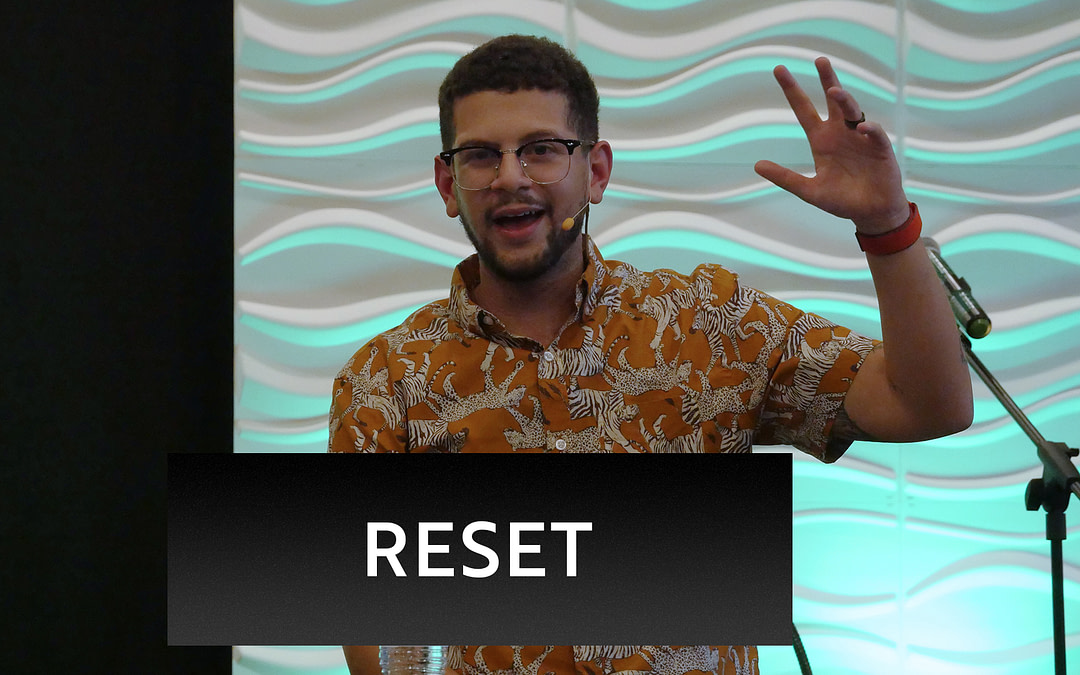 """Pastor Jacob preaching his message from Reset. Green lit backdrop and white, wavy tiles are in the background. The word """"Reset"""" on the bottom third of the image."""